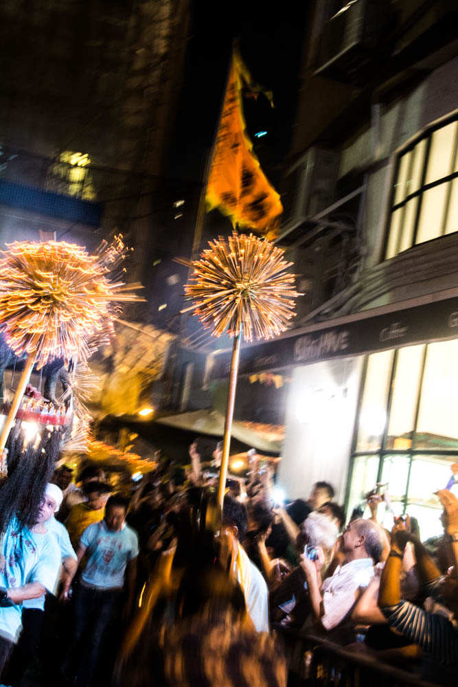 Large, round pompoms of incense precede the dragon.