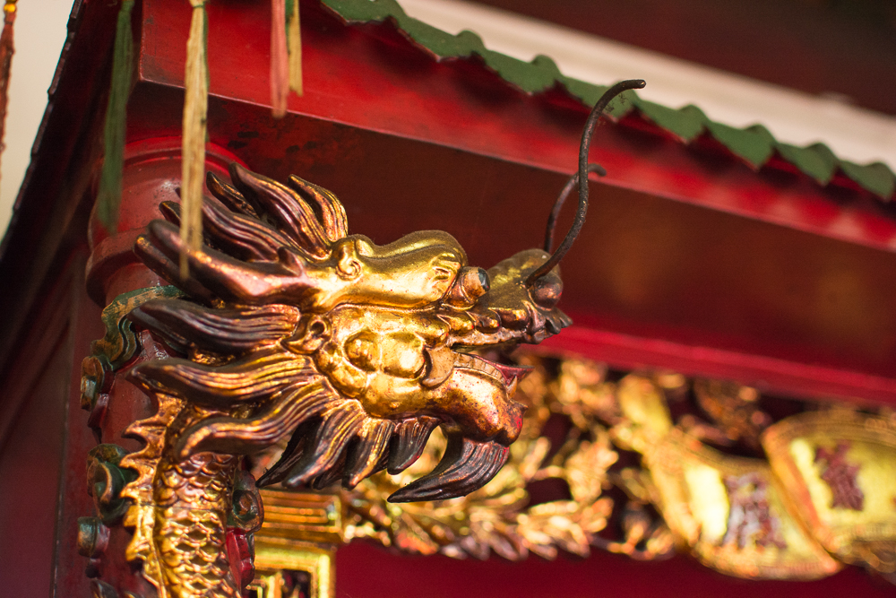 A fierce looking dragon stands outside the temple.